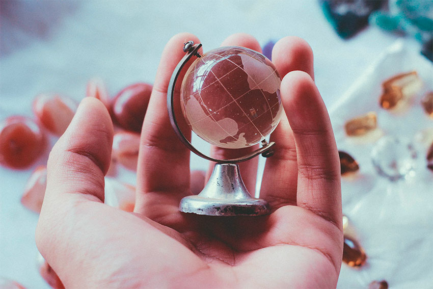 hand holding a toy miniature earth globe